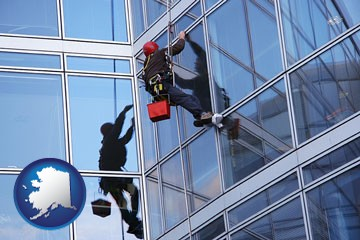 a window washer, washing office building windows - with Alaska icon