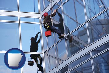 a window washer, washing office building windows - with Arkansas icon