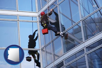 a window washer, washing office building windows - with Arizona icon