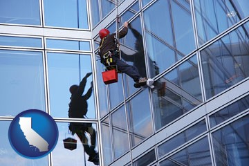 a window washer, washing office building windows - with California icon