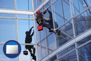 a window washer, washing office building windows - with Colorado icon