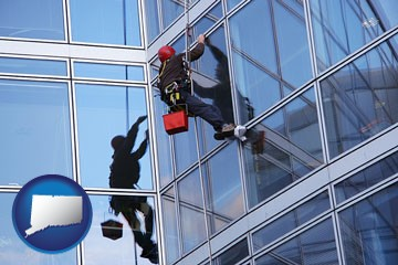 a window washer, washing office building windows - with Connecticut icon