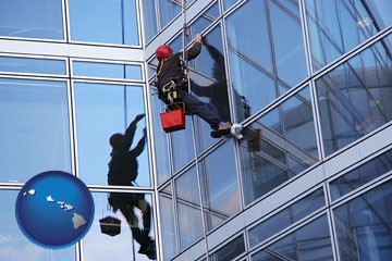 a window washer, washing office building windows - with Hawaii icon