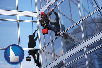 a window washer, washing office building windows - with Idaho icon