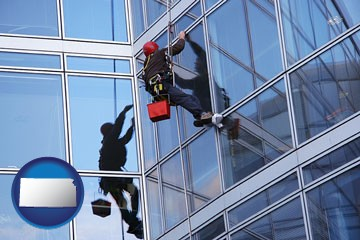 a window washer, washing office building windows - with Kansas icon