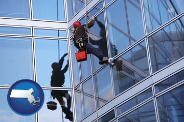 a window washer, washing office building windows - with Massachusetts icon