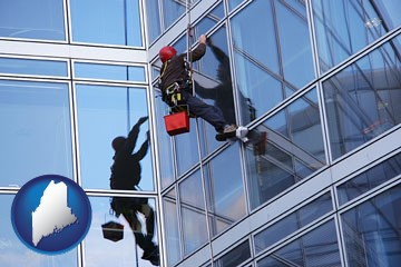 a window washer, washing office building windows - with Maine icon
