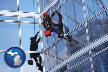 a window washer, washing office building windows - with Michigan icon