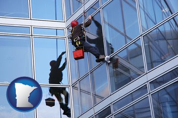 a window washer, washing office building windows - with Minnesota icon