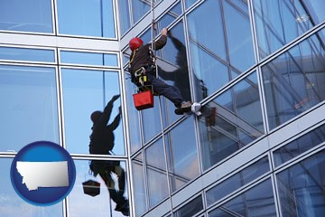a window washer, washing office building windows - with Montana icon