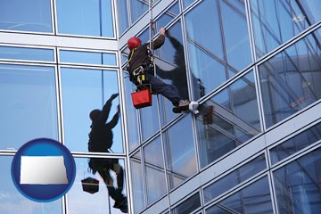 a window washer, washing office building windows - with North Dakota icon