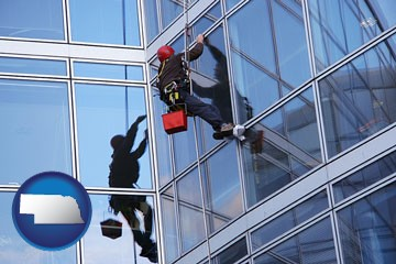a window washer, washing office building windows - with Nebraska icon
