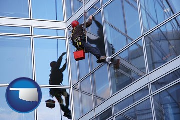 a window washer, washing office building windows - with Oklahoma icon