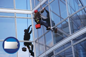 a window washer, washing office building windows - with Pennsylvania icon