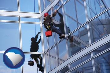 a window washer, washing office building windows - with South Carolina icon