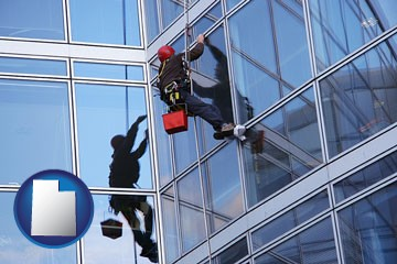 a window washer, washing office building windows - with Utah icon