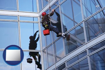 a window washer, washing office building windows - with Wyoming icon